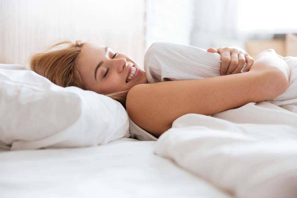 Side view of smiling woman emracing with pillow